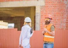Construction site safety inspection. Discuss progress project. Woman inspector and bearded brutal builder discuss stock photo