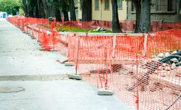 Construction site safety net fence as barrier parallel with the pipeline trench on the street in the city . Construction site safety net fence as barrier royalty free stock images
