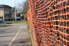 Construction site with safety orange fence. Warning sign on the street Royalty Free Stock Photo