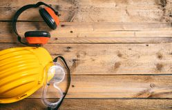 Construction safety. Protective hard hat, headphones and glasses on wooden background, copy space, top view Royalty Free Stock Images