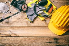 Construction safety. Protective hard hat, headphones, gloves and glasses on wooden background, copy space, top view Stock Photo