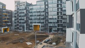 Construction site with scaffold, building work process modern an apartment panel house. Decoration and cladding of