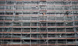 Construction site scaffolding. Big scaffolding on a contruction site compiling a symmetric lineal structure Stock Photos