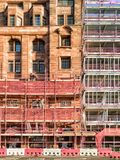 Construction site with scaffolding and safety measures. Construction of a new structure adjacent to an old historic building  with a scaffolding on Stock Image