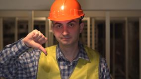 On a construction site, serious worker or engineer is not happy making a dislike gesture