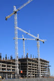 Construction Site. Several cranes with a blue sky background are setup and working at construction site where a building is being built Royalty Free Stock Photo