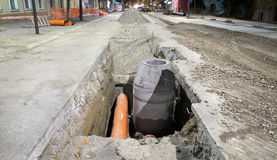 Construction site, sewerage in city. Hydro construction work, reconstruction of sewerage, night photo Royalty Free Stock Image