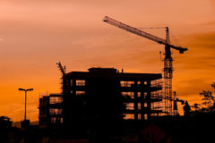 Construction site silhouette. Silhouette of Crane and Building Construction Site Stock Photos