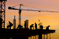 Construction site silhouette. Silhouette of hardworking men on construction site at sunset Stock Photography