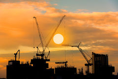 Construction site silhouette on tower building rooftop twilight Stock Photo