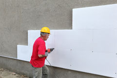 Construction site, styrofoam insulation drilling for anchor. Worker drilling styrofoam sheet insulation on the wall royalty free stock images