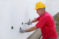 Construction site, styrofoam insulation. Worker placing expansion anchor to styrofoam sheet insulation of the wall with hammer Royalty Free Stock Photography