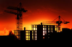 Construction site at orange sunset. A construction site silhouetted by dramatic orange sunset showing the major parts of the building structure and cranes royalty free stock photo