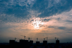 Construction site on sunset. Construction cranes silhouette at sunrise Stock Photography