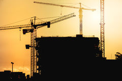 construction site at sunset with silhouettes of tower cranes royalty free stock photography