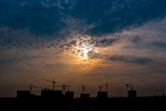 Construction site sunset wide view. Construction cranes silhouette at sunrise Royalty Free Stock Photos