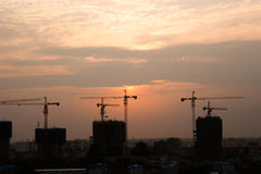 Construction site sunset wide view. Construction cranes silhouette at sunrise Royalty Free Stock Image