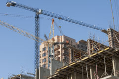Construction site with tall cranes. And metal deck in the foreground Royalty Free Stock Images