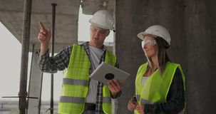 Construction site team or architect and builder or worker with helmets discuss on a scaffold construction plan or
