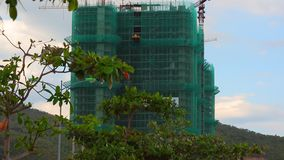 Construction site tower cranes Asian hotel. High rise tower cranes on a Vietnamese construction site, under construction and scaffolding covered in protection stock video footage