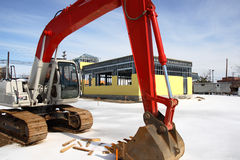 Construction Site Tractor. Tractor parked on snow with a background of steel frame building half way done royalty free stock photography