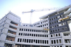 Construction Site with Unfinished Building. A wide angle shot of an unfinished building and a lift crane on construction site Royalty Free Stock Photo