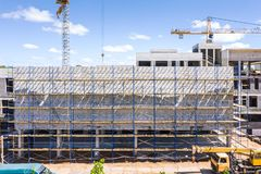 Construction site with unfinished building covered in scaffolding stock images