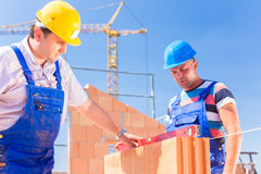 Construction site worker checking building walls royalty free stock images