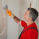 Construction site, worker installing gypsum board Stock Image