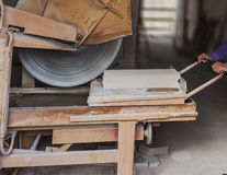 Construction site: Worker with machine cutting blocks Royalty Free Stock Photography
