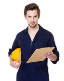 Construction site worker with protective hat and clipboard Royalty Free Stock Image