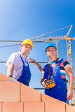 Construction site workers building house with crane Royalty Free Stock Image