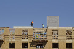 Construction site workers building roof on apartment complex Royalty Free Stock Image