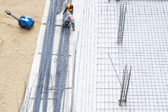 Construction site Workers on cement floor Steel Rods Base Building Stock Images