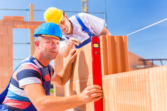 Construction site workers checking  building shell. Construction site workers or bricklayer with helmets controlling building walls with a bubble level Royalty Free Stock Images