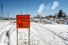 Construction Site Workers Zone Sign. On a bright winter day with power lines and towers on a cloudy sky stock photography