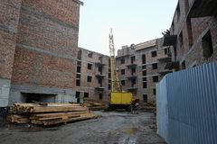 Construction site with yellow crane and not finished residential building. Kolomyia, Ukraine royalty free stock photo