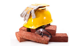 At the construction site. Yellow helmet, gloves, goggles and red-burned bricks on a white background Stock Images