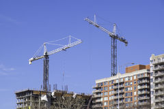Construction sites with cranes and highrises. Cranes on top of highrise buildings in a modern city with blue sky royalty free stock image