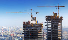 The Construction of the skyscraper. Two skyscrapers. Two crane on background blue sky Royalty Free Stock Photos