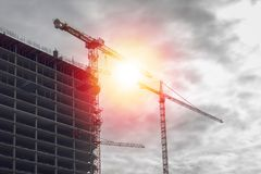 Construction of skyscraper with cranes in sunset. Construction of skyscraper frame with cranes in sunset Royalty Free Stock Images