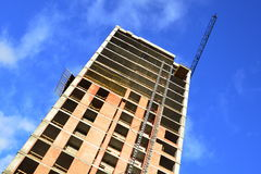 Construction of a skyscraper monolith. And brick construction elements from a number of tower crane Royalty Free Stock Photo