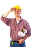 Construction smiling into the camera. Handsome man - builder with drawings smiles and adjusts his helmet hand royalty free stock image