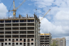 Construction of solid-brick houses, tower cranes on a background. Construction of two monolith-brick apartment buildings Stock Image