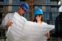 Construction specialists reviewing bluprints Stock Image