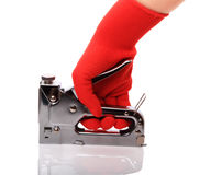 Construction stapler. Building a stapler in his hand in the red gloves isolated on white background stock image