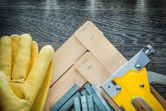 Construction stapler staples wooden planks leather protective gl. Oves royalty free stock photography