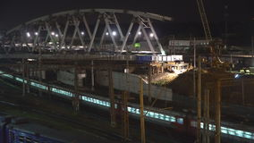 The construction of a steel bridge and night movement of trains on a railway junction. Moscow stock footage