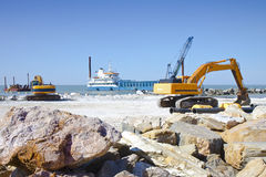 Construction of a stone dam to protect the shore from the sea wa Stock Image