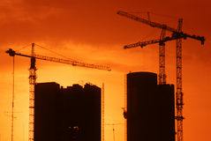 Construction at sunset. Two cranes putting up new buildings back lit by sunset Stock Photography